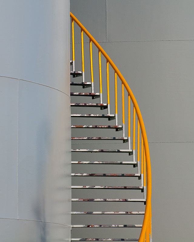 staircase with yellow railing
